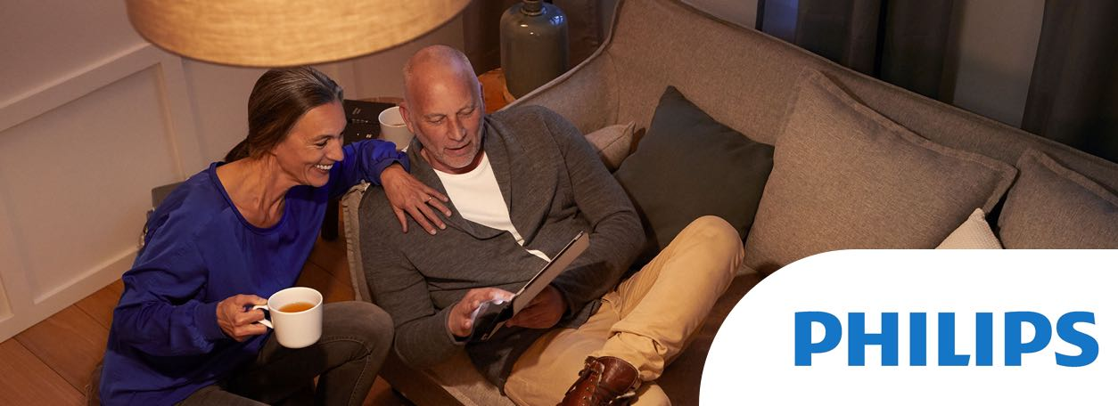 Philips logo with couple reading under light on couch